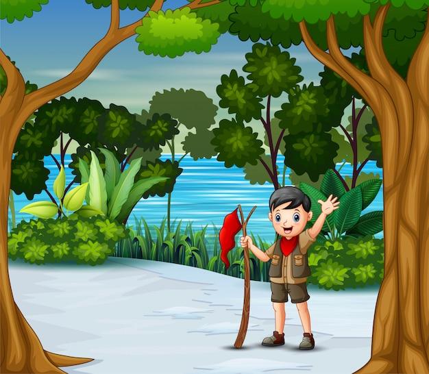 冬の森の赤い旗を持つスカウト少年