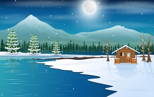 湖のほとりの木造の小さな家のある冬景色