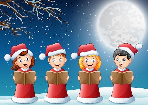 冬にクリスマスキャロルを歌う赤いサンタ衣装の子供たち