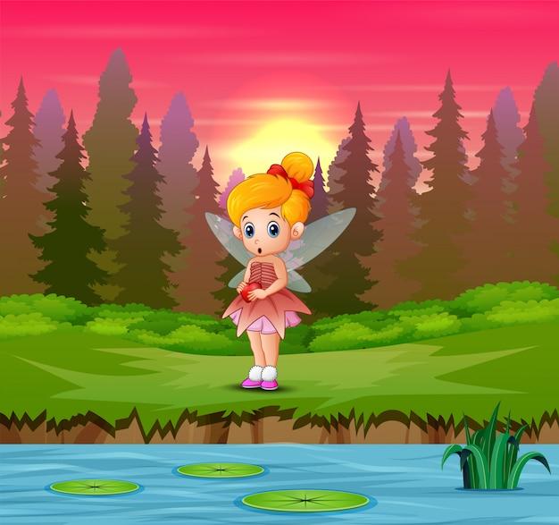 リバーサイドに立っているかわいい小さな愛の妖精