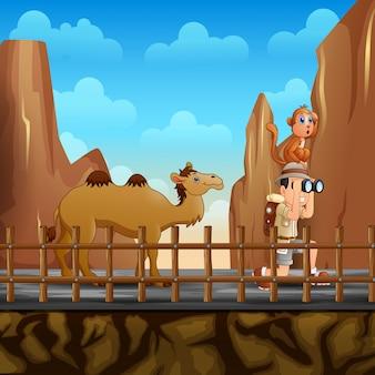 岩の近くの丘の上で他の動物を見ている探検家の少年