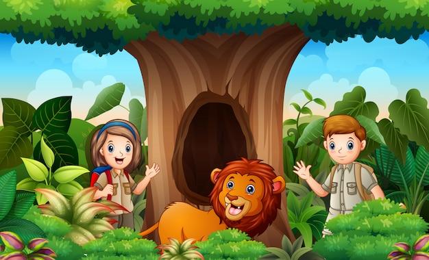 中空の木の下の飼育係とライオン