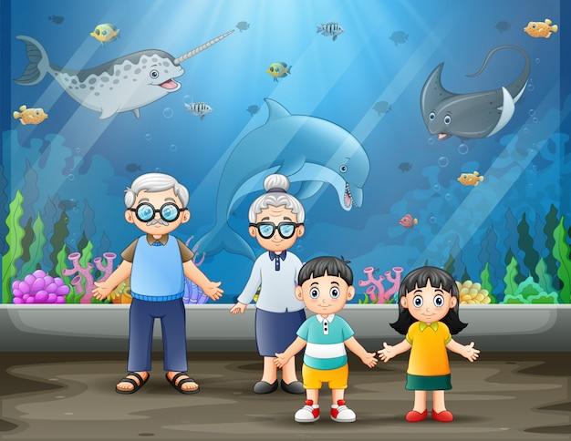 魚を見ている年配のカップルと孫