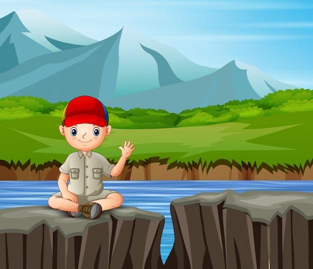 Исследователь мальчик сидит на скале