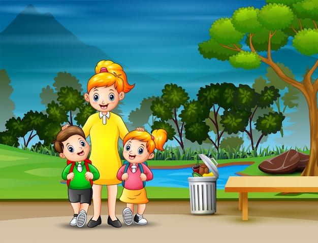 幸せな男の子と女の子が母親と一緒に学校に行く