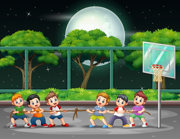 Группа мальчиков, играющих в перетягивание каната на площадке ночью