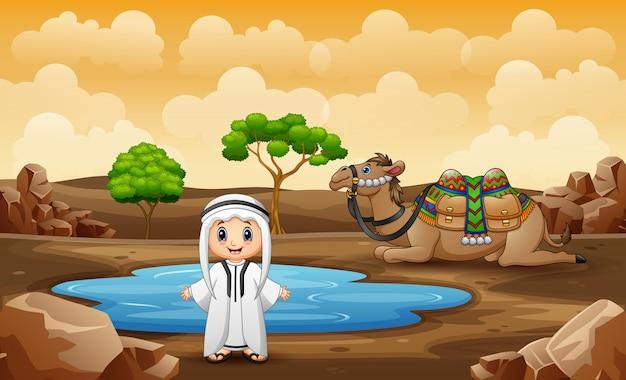 アラブの少年と砂漠の小さな池で休んでいるラクダ