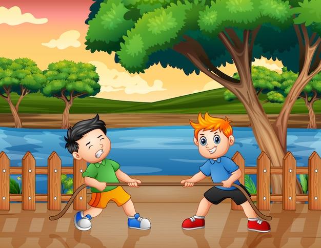 Два мальчика играют перетягивание каната на пирсе