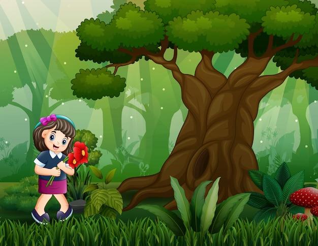 Счастливая девушка собирает цветы в лесу