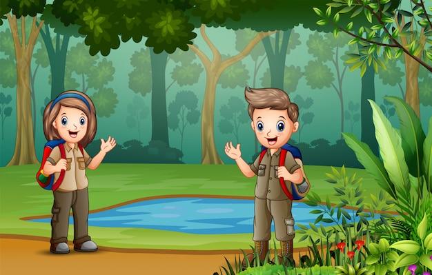スカウトの男の子と女の子が湖のほとりで休憩