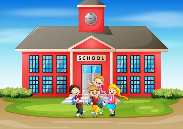 学校の前で楽しんでいる多くの子供たち