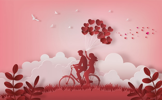 ハート形の風船を持っている片手で山の上に沿って乗って幸せなカップル。