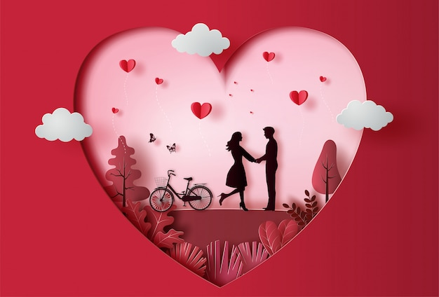 多くの心が浮かんでいる紙のアートスタイルの公園で手を繋いでいる若いカップル。