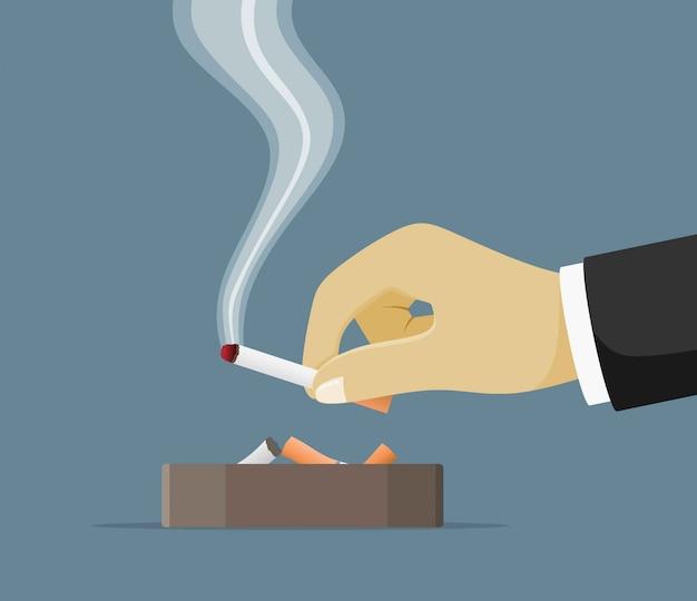 たばこの煙がいっぱいのセラミック灰皿。喫煙用食器。手にタバコ。