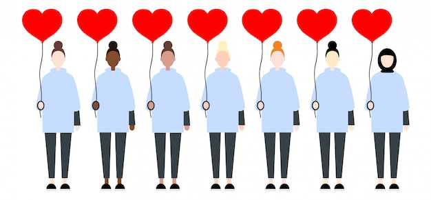 赤い風船の心を保持しているカジュアルな服装の女性
