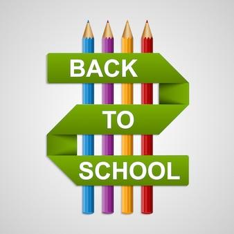 Цветные карандаши с текстом обратно в школу на бумажной ленте.