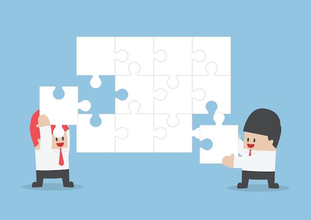 ビジネスマンは、空白のジグソーパズルを組み立てるためにお互いを助けます