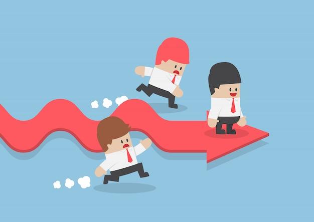 ビジネスマンは成功の矢印の上に立っている間彼のライバルより速く行きます