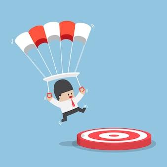 ターゲットに着陸するパラシュートフォーカスを持ったビジネスマン
