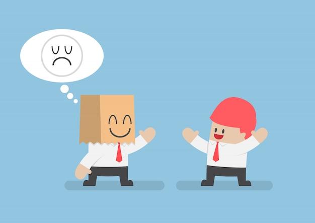 Бизнесмен скрывает свои грустные эмоции за улыбающимся бумажным пакетом