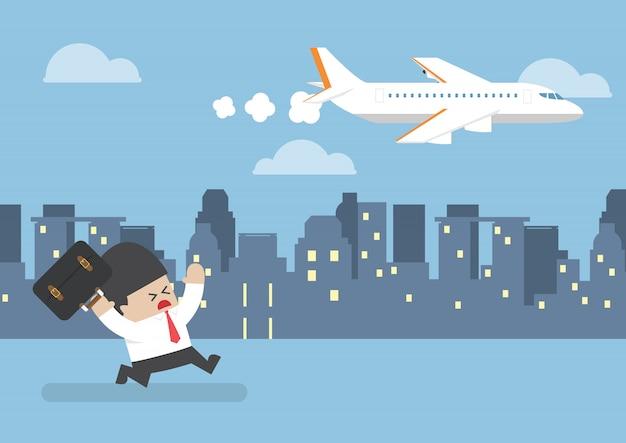飛行機の後ろを走る飛行を逃したビジネスマン