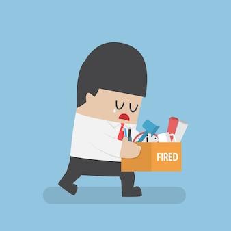 Уволенный бизнесмен держит коробку с личными вещами