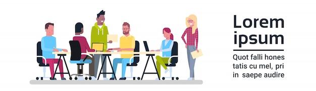 オフィスの机に座っているビジネス会議チームを働く創造的な人々のグループ