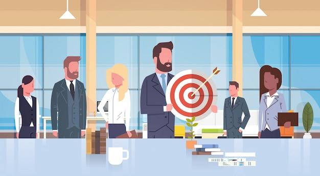 現代のオフィスでターゲットチームワークと戦略コンセプトミックスレースチームを保持しているビジネス人々のグループ