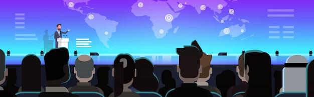 ビジネスマングループビジネスマンの前で世界地図上のビジネスプレゼンテーションをリードするビジネスマン