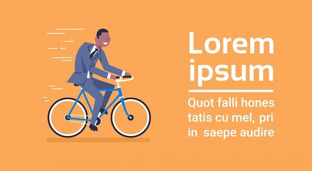 スーツを着たアフリカ系アメリカ人ビジネスマンコピースペースを持つテンプレート青い背景上の自転車に乗る