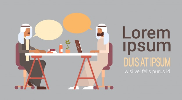 アラブのビジネスマンが話しているオフィスの机に座ってチャット通信を議論します。