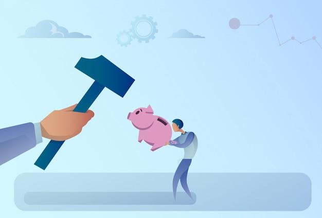 ビジネス男の手がハンマーで貯金を打つ