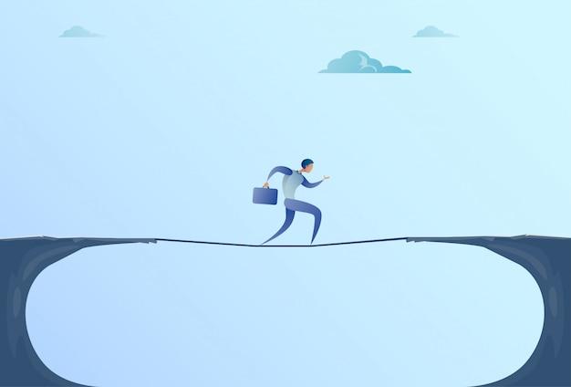 ビジネスマンの崖ギャップ山を越えて歩くビジネスマンのバランスをとる木の棒橋