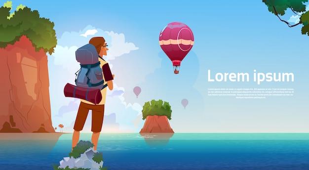 男バックパッカーは夏の冒険休暇の概念に山の湖の旅行者の眺めを楽しむ