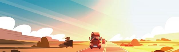 日没の景色の上の田舎道を運転する大きい半トラックのトレーラーが付いている横のバナー