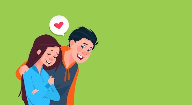 少年は抱擁少女ハート形画像コピースペースを持つ愛のバナーでかわいい十代の若者たち