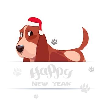 ハッピーニューイヤーグリーティングカードホリデーレタリングバナーにサンタの帽子でかわいいバセット犬