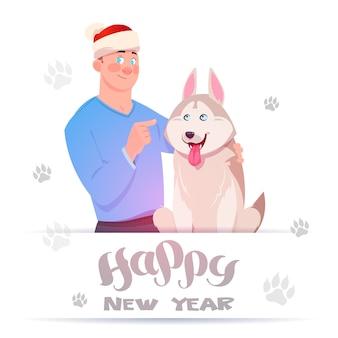 白い背景の上の足跡の上のかわいいハスキー犬を抱きしめるサンタ帽子の男と幸せな新年カード