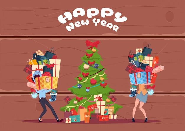 木製の織り目加工の背景、新年あけましておめでとうございます上のクリスマスツリーにプレゼントボックスのスタックをもたらすカップル