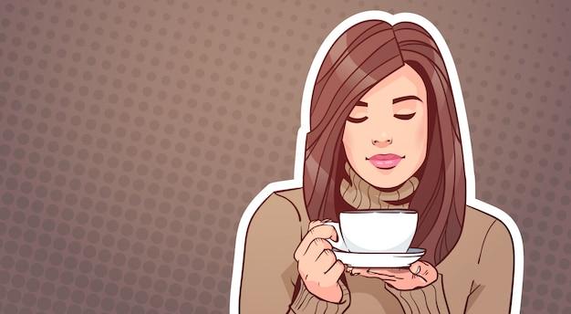 ビンテージポップアートの背景の上に熱い飲み物とカップを保持している美しい女性の肖像画