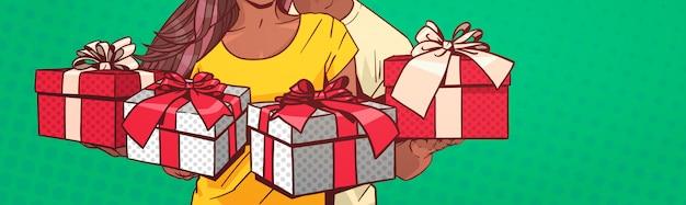 プレゼントボックスを保持している認識できないアフリカ系アメリカ人カップル水平バナーコミックピンアップれたら