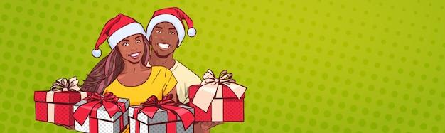 サンタ帽子をかぶっているアフリカ系アメリカ人カップルが幸せな男と女の水平方向のバナーを提示します。