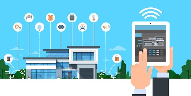 スマートホームシステムのコントロールインターフェースを備えたデジタルタブレットを持っている手現代家のオートメーションの概念
