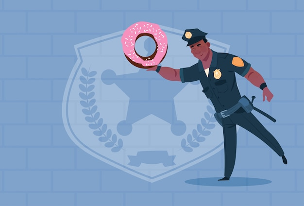 アフリカ系アメリカ人の警官はレンガの背景の上に制服警官ガードを身に着けているドーナツを保持します。