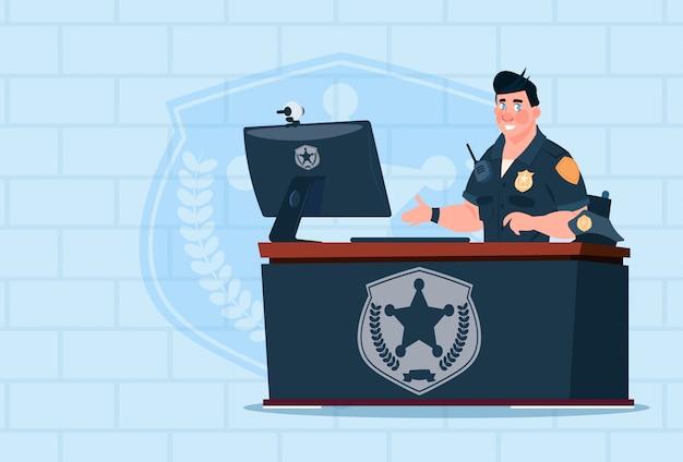 れんが造りの背景上の監視事務所で制服警官を着てコンピューターに取り組んでいる警官