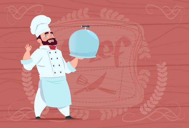 木製の織り目加工の背景の上に白いレストラン制服を着た漫画の料理笑顔でシェフクックトレイ