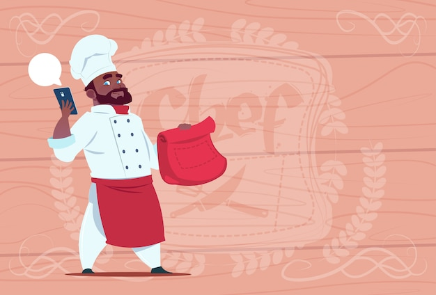 アフリカ系アメリカ人シェフの料理と携帯電話でパケットを保持レストランの配達コンセプトチーフ木製テクスチャ背景
