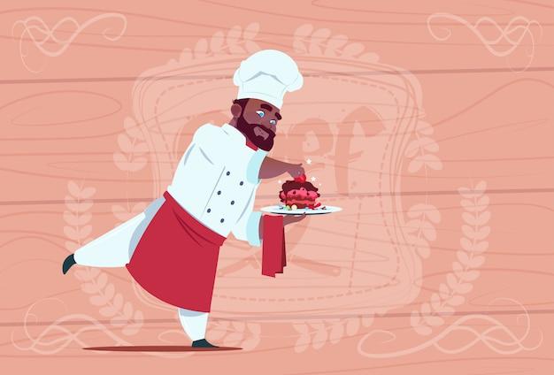木製の織り目加工の背景の上の白いレストラン制服を着たデザート皿笑顔漫画チーフを保持しているアフリカ系アメリカ人シェフ料理