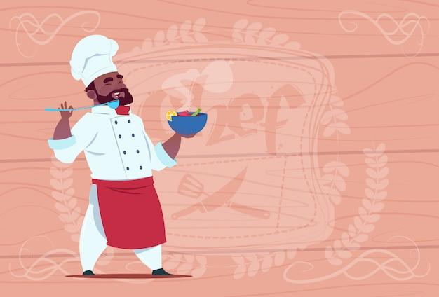 木製の織り目加工の背景の上の白いレストランの制服を着たホットスープ笑顔漫画チーフとアフリカ系アメリカ人シェフクックプレート