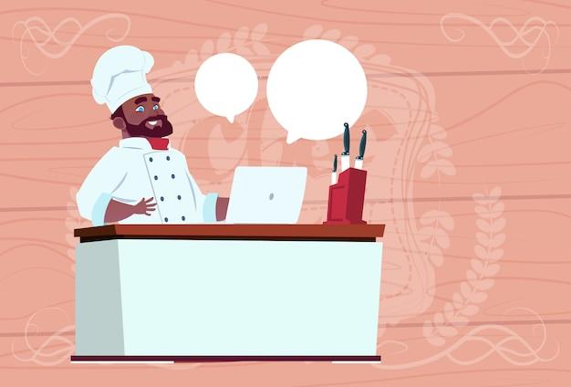 白い制服を着たラップトップコンピューター漫画レストランチーフで働いているアフリカ系アメリカ人シェフクック木製のテクスチャ背景の上の机に座ってください。